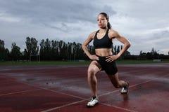 Précipitez l'exercice pour le quadriceps par l'athlète sur la piste images stock
