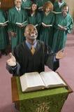 Prédicateur heureux avec la bible à l'autel d'église recherchant la vue courbe photo stock