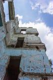 Prédio da escola coberto de vegetação abandonado velho Foto de Stock
