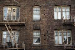 Prédio de apartamentos do tijolo do cortiço dos escapes de Windows e de fogo Imagem de Stock