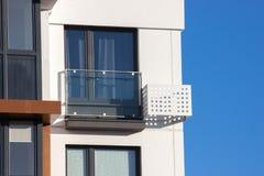Prédio de apartamentos no canto da construção, cortinas da janela no assoalho Cerca de vidro na caixa da fachada e do condicionam foto de stock