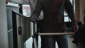 Prédio de escritórios do sistema de segurança da tecnologia do toque do acesso da porta da entrada com os businessmans que vão tr video estoque