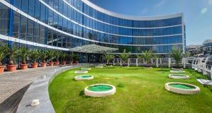 Prédio de escritórios moderno com uma fachada de vidro e um gramado verde foto de stock royalty free
