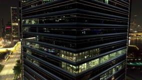 Prédio de escritórios moderno na noite A noite ilumina-se, baixa do prédio de escritórios da cidade, opinião da arquitetura da ci filme