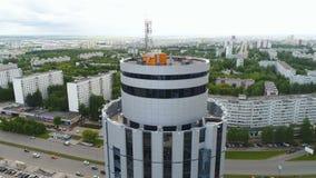 Prédio de escritórios redondo contra a antena moderna da cidade filme