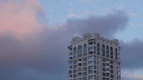 Prédio no fundo do céu com as nuvens moventes no por do sol video estoque