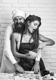 Prélude - couple dans l'amour Fille ou belle femme dans le tablier rouge malpropre avec de la farine sur la cuisine blanche Images libres de droits