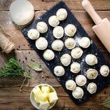 Préparant, faisant cuire, faisant les ravioli faits maison, pelmeni ou boulette avec de la viande sur la vue supérieure en bois d Photo stock