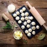 Préparant, faisant cuire, faisant les ravioli faits maison, pelmeni ou boulette avec de la viande sur la vue supérieure en bois d Images stock