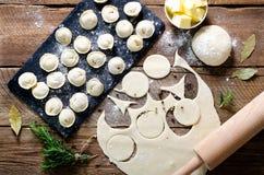 Préparant, faisant cuire, faisant les ravioli faits maison, pelmeni ou boulette avec de la viande sur la vue supérieure en bois d Image libre de droits