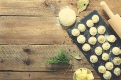 Préparant, faisant cuire, faisant les ravioli faits maison, pelmeni ou boulette avec de la viande sur la vue supérieure en bois d Image stock