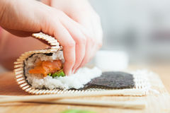 Préparant, sushi de roulement Saumons, avocat, riz et baguettes sur la table en bois Photographie stock