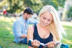 Préparation aux essais Le joli fille-étudiant indique le manuel et le smil Images stock