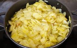 Préparation d'une omelette espagnole traditionnelle sur la poêle espagnol Photo stock