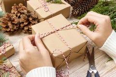 Préparation de cadeaux de Noël Le boîte-cadeau enveloppé dans le papier rayé noir et blanc, une caisse complètement de cônes de p Photo stock
