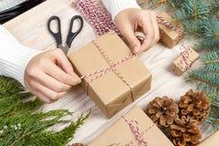 Préparation de cadeaux de Noël Le boîte-cadeau enveloppé dans le papier rayé noir et blanc, une caisse complètement de cônes de p images stock
