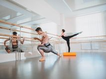 Préparation de corps avant représentation dans le studio de ballet Danseur masculin et ballerine réchauffant près du barre sur la photo stock
