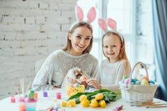 Préparation de Pâques La petite fille avec sa course de mère un lapin décoratif à la maison photos stock