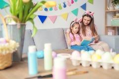 Préparation de Pâques de mère et de fille ensemble à la maison dans le livre de lecture d'oreilles de lapin Images libres de droits
