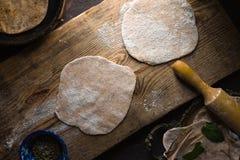 Préparation de pain de chapati sur la vue supérieure de conseil en bois images libres de droits