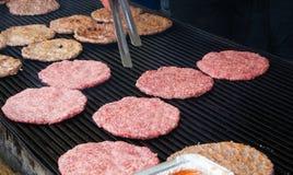 Préparation de petits pâtés d'hamburger sur le gril de barbecue au marché en plein air croate Photos stock