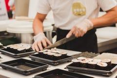 Préparation de petits pains de sushi au festival de l'Orient à Milan, Italie Image stock