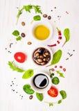 Préparation de salade avec des habillages, des olives, des feuilles sauvages d'herbes, le piment, le pétrole et des tomates Photographie stock libre de droits