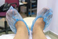 Préparation des pieds pour une pédicurie Pieds dans des couvertures de chaussure image stock