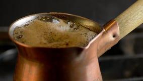 Préparation du café turc dans le cezve de cuivre sur la cuisinière à gaz clips vidéos