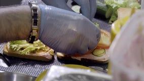Préparation du sandwich avec le sandwich à jambon et à fromage suisse sur le pain blanc Plan rapproché le cuisinier prépare un sa clips vidéos