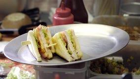 Préparation du sandwich avec le sandwich à jambon et à fromage suisse sur le pain blanc Plan rapproché le cuisinier prépare un sa banque de vidéos