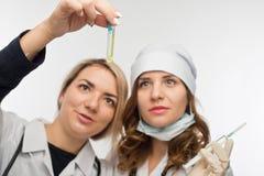 Préparation pour donner une injection par les jeunes professionnels de la santé Photo stock