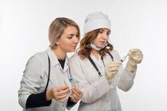 Préparation pour donner une injection par les jeunes professionnels de la santé Photos libres de droits