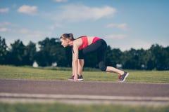 Préparez pour aller ! Athlète féminin sur la ligne de départ d'un stade TR Photographie stock