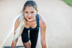 Préparez pour aller ! L'athlète féminin dans une chemise bleue et les guêtres sur la ligne de départ d'un stade dépistent regarde Photographie stock