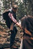 Préparez toujours pour aider Jeunes couples modernes tenant des mains et le movi images libres de droits