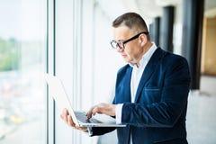 Préparez toujours pour vous aider Homme mûr gai dans le formalwear ajustant ses lunettes et tenant l'ordinateur portable tout en  photo libre de droits