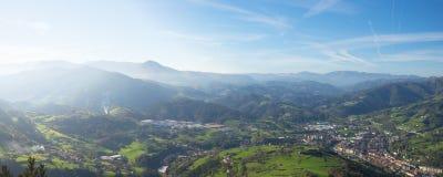 Prés et maisons de montagnes avec la ville de Tolosa Image stock