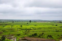 Prés verts luxuriants et ciel obscurci de mousson photos stock
