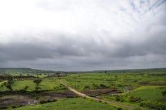 Prés verts luxuriants et ciel obscurci de mousson image libre de droits