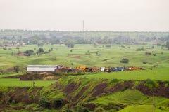 Prés verts luxuriants et ciel obscurci de mousson près d'un site minier images stock