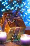 Présent d'or allumé par des bougies Photo stock