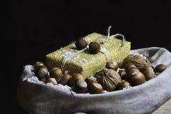 Présent et écrous dans un sac rustique couvert de neige Photographie stock