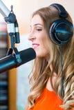 Présentateur par radio féminin dans la station de radio sur l'air photographie stock libre de droits