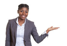 Présentation d'une femme africaine riante d'affaires Photographie stock libre de droits