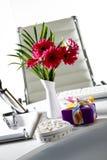 Présents et vase à fleur sur la table de bureau Photographie stock libre de droits