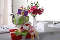 Présents et vase à fleur sur la table de bureau Images libres de droits