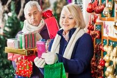 Présents heureux d'achats de femme avec l'homme fatigué Photos stock
