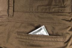 Préservatif dans la poche arrière de pantalon brun Images stock