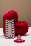 Préservatif oral de pilules contraceptives sur le coeur rouge Photos stock